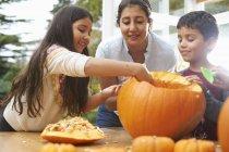Матері і діти спустотаючи гарбуза в їдальні — стокове фото