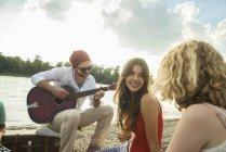 Молода людина з друзями, грати на гітарі — стокове фото