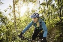 Молодая женщина на горном велосипеде через лес, озеро Комо, Италия — стоковое фото