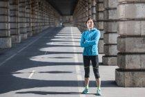 Portrait of mature female runner in sunlit arcade — Stock Photo