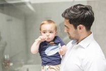 Vater hält kleinen Sohn beim Zähneputzen — Stockfoto