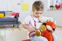 Girl playing doctor to soft toys — Stock Photo