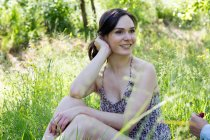 Young woman sitting on grass looking away smiling — Stock Photo