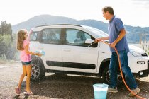 Grandfather and granddaughter washing car — Stock Photo