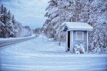 Tradicional ponto de ônibus na esquina da neve coberta de estradas rurais, Hemavan, Suécia — Fotografia de Stock