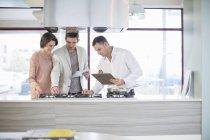 Взрослая пара и продавец смотрят на плиту в кухонном салоне — стоковое фото