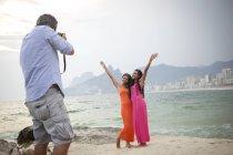 Veduta posteriore dell'uomo che fotografa due giovani donne sulla spiaggia di Ipanema, Rio De Janeiro, Brasile — Foto stock