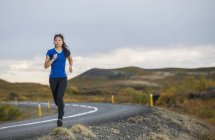 Mid adult woman running on road in rural landscape — Stock Photo