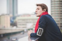 Young male runner looking out over city from rooftop — Stock Photo