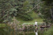 Man on fallen tree near lake, Valle de Aran, Spain — Stock Photo