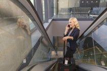 Mi femme adulte détenant la valise sur l'escalator à l'aide de smartphone, à la recherche de suite souriant — Photo de stock