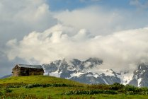 Barn on hill and distant mountains with cloudy sky — Stock Photo
