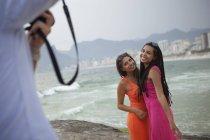 Foto ritagliata di uomo che fotografa due giovani donne sulla spiaggia di Ipanema, Rio De Janeiro, Brasile — Foto stock