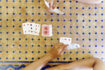 Overhead cropped shot of mature woman and son playing cards at table — Stock Photo