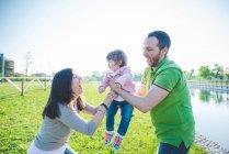 Парочка раздающих дочку в парке — стоковое фото
