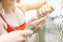 Young women using smartphone beside fence — Stock Photo