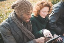 Young man and woman using touchscreen on digital tablet in park — Stock Photo