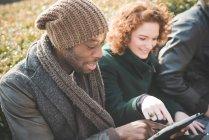 Hombre joven y mujer utilizando la pantalla táctil en una tableta digital en el Parque - foto de stock