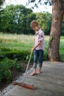 Boy sweeping the porch — Stock Photo