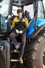 Фермер с помощью мобильного телефона на тракторе — стоковое фото