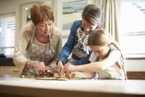 Femme âgée et petites-filles décorant biscuits sapin de Noël — Photo de stock
