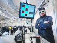 Cientista masculino em desgaste protetor e óculos sorrindo para a câmera em laboratório — Fotografia de Stock