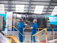 Aircraft engineers discussing 737 jet engine in airport — Stock Photo