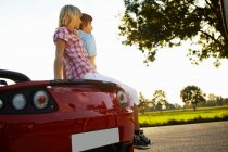 Couple sitting on their electric car — Stock Photo