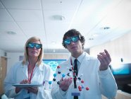 Scientifique et apprenti en lunettes 3D tenant modèle moléculaire et tablette numérique — Photo de stock