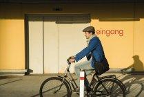 Молода людина, їзда на велосипеді уздовж міських вулиць — стокове фото
