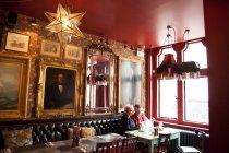 Pareja extraña relajándose en el bar y restaurante, Bournemouth, Inglaterra - foto de stock