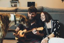 Couple sitting on apartment floor holding dog's paw — Stock Photo