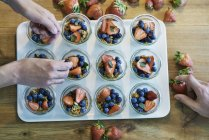 Cropped image of Chefs preparing desserts with blueberries and strawberries — Stock Photo