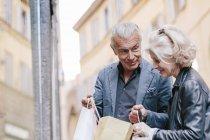 Touristen-paar auf der Suche in Einkaufstüten auf Stadtstraße, Siena, Toskana, Italien — Stockfoto
