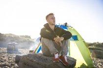 Jeune campeur mâle assis sur la plage rocher — Photo de stock