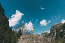 Bare chested young male standing on boulder top — Stock Photo