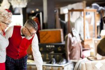 Quirky vintage couple looking down in antiques and vintage emporium — Stock Photo