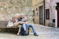 Coppia di turisti seduti su panca guardando tablet digitale a Siena, Toscana, Italia — Foto stock