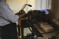 Середине части женского ювелир с использованием пылающий факел удар на верстак — стоковое фото