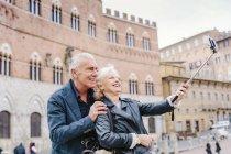 Tourist couple using selfie stick in city, Siena, Tuscany, Italy — Stock Photo