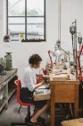 Female jeweler using coping saw at workbench — Stock Photo