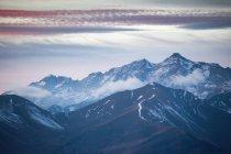 Majestätische Landschaft mit Nebel über den Bergen und wolkenverhangenem Himmel bei Sonnenuntergang — Stockfoto