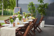 Table prepared with flower arrangements and plates for lunch on patio — Stock Photo