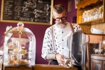 Quirky vintage senior man using coffee machine in tea room — Stock Photo