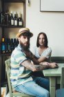Portrait of cool couple at bar table — Stockfoto