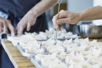 Chef colocando pastelería en bandeja para hornear - foto de stock