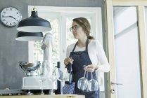 Caterer feminino segurando copos de vinho e garrafa de vinho — Fotografia de Stock