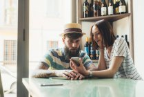 Couple looking at smartphone at bar table — Stock Photo