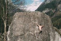 Vista posteriore del giovane che si arrampica sul masso — Foto stock