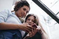 Две ювелирки ищут смартфон в ювелирной мастерской — стоковое фото